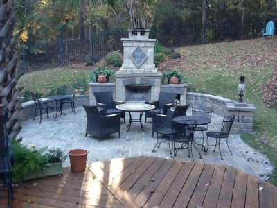 This deck in Irmo SC overlooks a serene hardscape patio with outdoor fireplace