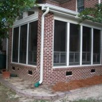 This vinyl four-track aluminum three season room with brick exterior blends seamlessly with home in Columbia. SC