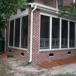 This vinyl fourtrack aluminum three season room with brick exterior blends seamlessly with home