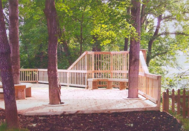 This lakeside pressure treated deck includes built in bench seating, and unique privacy railing. We also integrated the existing trees within the landscape into the design of the deck- stunning.