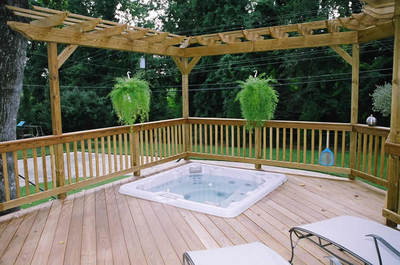 This pressure treated wood pergola provide a sense of space definition around this hot tub deck