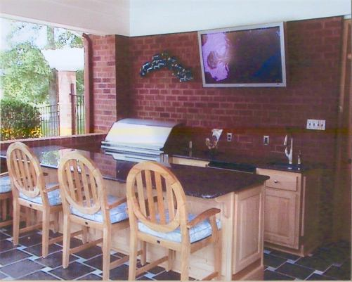 This covered patio space features an outdoor kitchen with bar seating and a wall-mounted TV