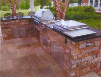 """This multi-functional outdoor kitchen features """"eat-in"""" style bar seating"""