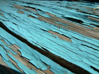 Peeling blue paint on wood deck.