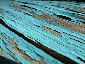 Peeling blue paint on wood deck.